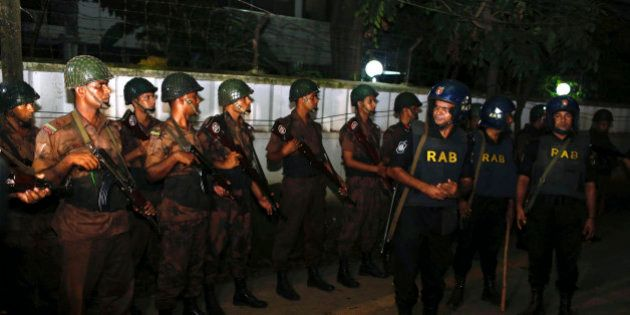 Bangladeshi security personnel cordon off the area after a group of gunmen attacked a restaurant popular...