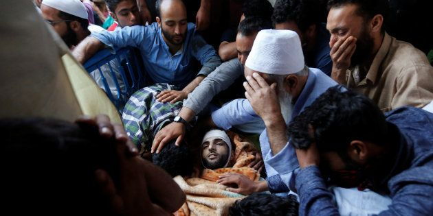 Family members and relatives mourn next to the body of Burhan Wani, a separatist militant leader, during...