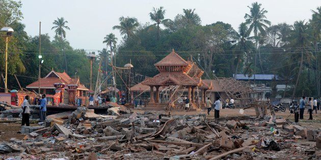 Indian bystanders gather among debris and building wreckage of The Puttingal Devi Temple in Paravur some...