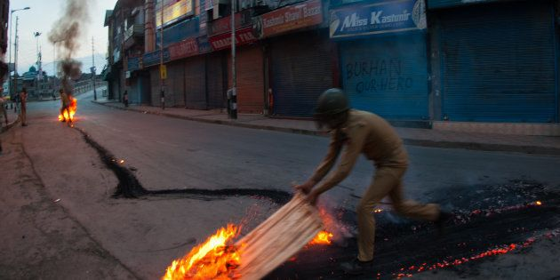 SRINAGAR, KASHMIR, INDIA - JULY 10: Indian government forces douse a burning tire left by the Kashmir...
