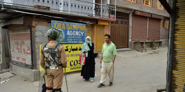 An Indian paramilitary trooper stops a Kashmiri couple during a curfew in Srinagar on July 12,