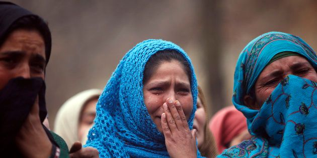 Kashmiri villagers weep during the funeral procession of Raqib Bashir, a suspected militant, in Zadura...