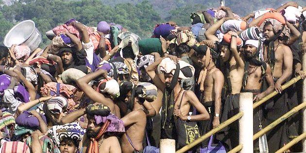 Hindu pilgrims queue outside the Sabarimala Temple to offer prayers tothe Hindu