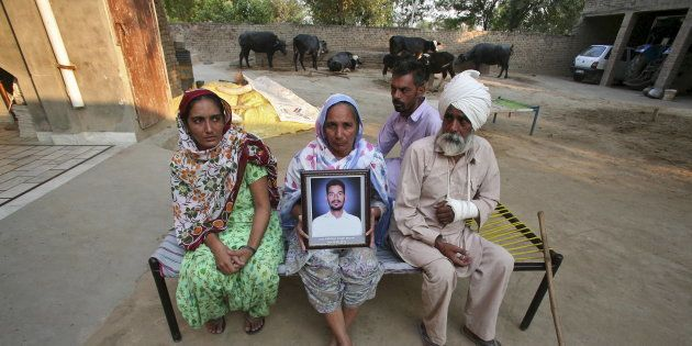 Malkit Kaur, mother of Kuldeep Singh, a cotton farmer who committed suicide, holds his portrait as Kuldeep's...