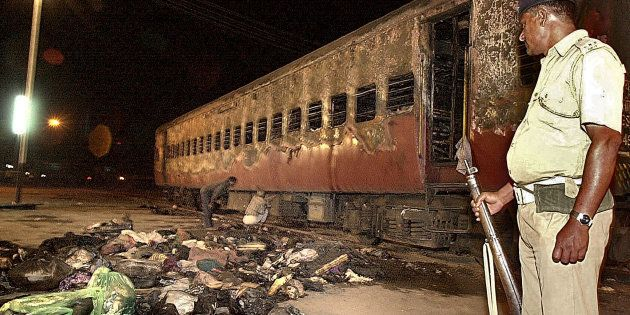 GODHRA, INDIA: A policeman looks over a burnt coach and belongings of Hindu activists at Godhra station,...