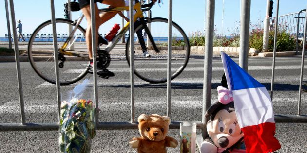 A man cycles past a bouquet of flowers, stuffed toys and a French flag placed in tribute to victims,...