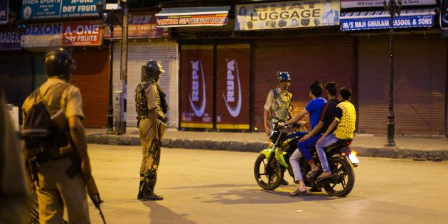 SRINAGAR, KASHMIR, INDIA - JULY 10: Indian government forces a motorcyclist in the City center to stop...