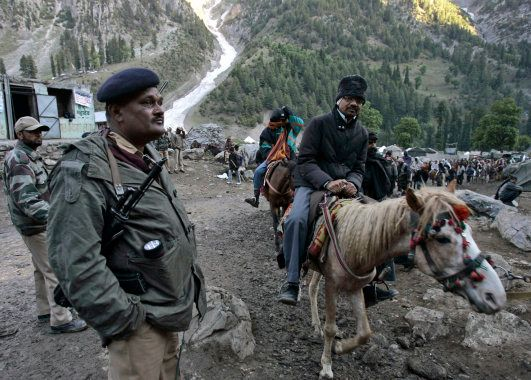 File photo of an Indian police officer keeping guard as Hindu pilgrims on horses proceed to reach the...
