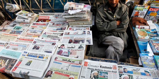 A newspaper vendor displays newspapers with cover stories of Osama bin Laden, in Srinagar, May 3, 2011....