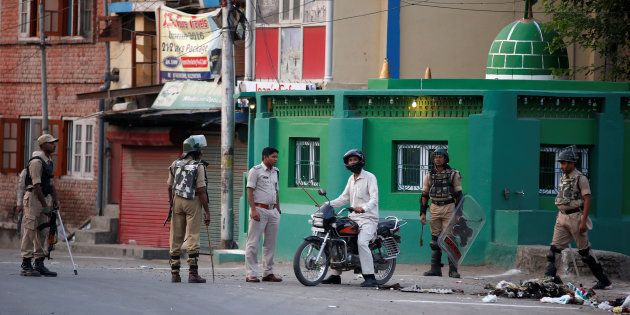 An Indian police officer stops a motorcyclist during a curfew in Srinagar July 13, 2016. REUTERS/Danish