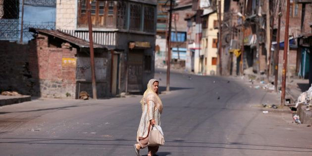 A woman crosses a deserted road during a curfew in