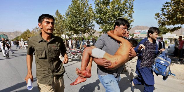 An injured boy is carried to a hospital after an explosion struck a protest in Kabul, Afghanistan, Saturday,...