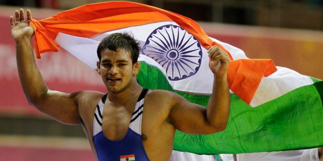 India's Narsingh Pancham Yadav holds his national flag as he celebrates winning the gold medal in the...