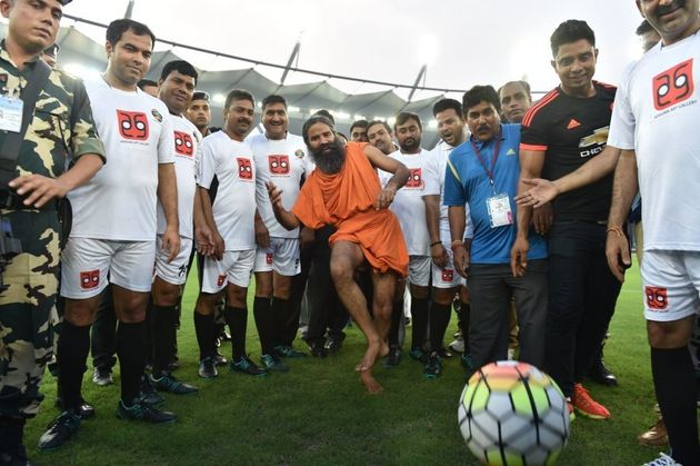Baba Ramdev kicks a football ahead of a football match in New