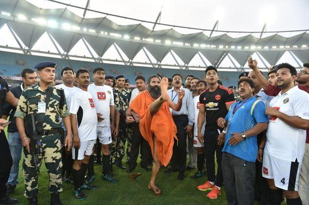 Indian yoga guru Baba Ramdev kicks a football ahead of a charitable football match between Indian Bollywood...