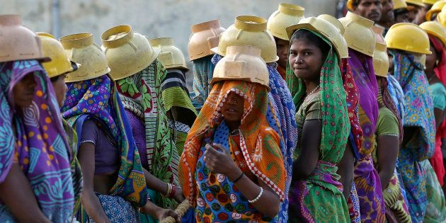 Female labourers wearing helmets take a break from laying underground electricity cables in Ahmedabad, India, March 7, 2016. REUTERS/Amit Dave TPX IMAGES OF THE DAY
