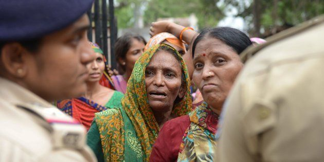 A Dalit woman waits for a relative's release from a police station after protestors were detained by...