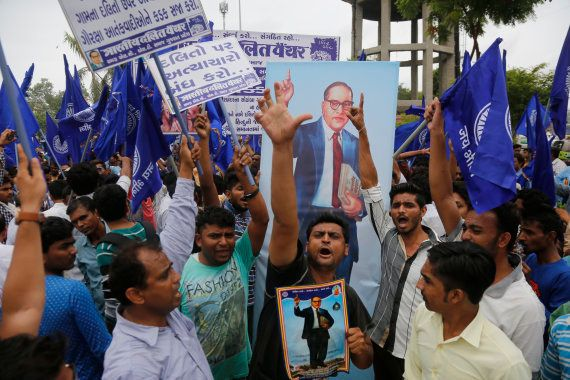 Dalits hold portraits of prominent freedom fighter Bhim Rao Ambedkar and protest against the alleged...
