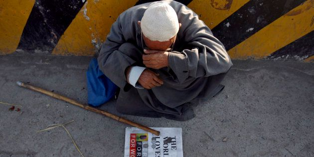 An elderly man sits along a street as he waits for alms in Srinagar August 8, 2007. REUTERS/Adnan