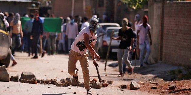 A demonstrator hurls a stone during a protest in Srinagar against the recent killings in
