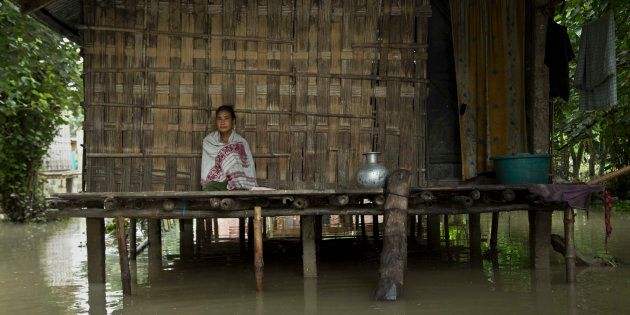 An Indian Mishing tribal woman sits at her traditional hut surrounded by flood waters at