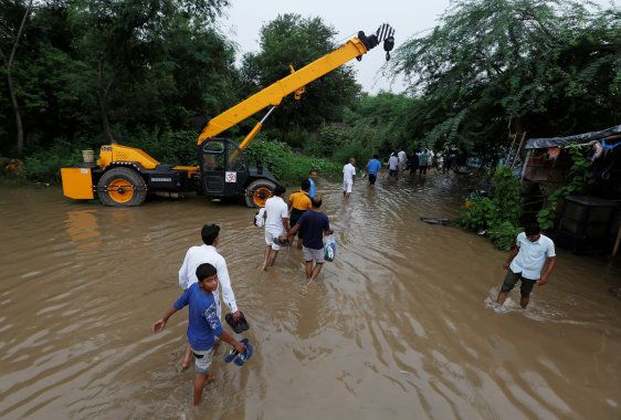 People wade through a waterlogged street next to a highway after heavy rains in Gurugram. REUTERS/Adnan