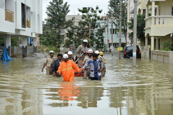 Members of the fire forces and volunteers participate in relief operations in a low lying flooded area...