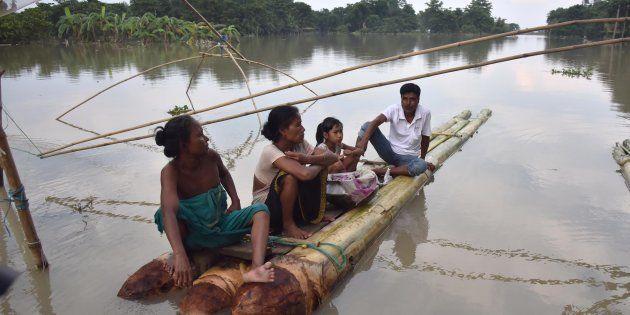 Indian villagers take rest on a raft in the flood-affected Bordiya Kacharigoan village in