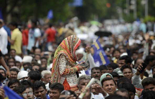 A supporter of Dalit community plays functions on her mobile phone as she crosses during a protest rally...