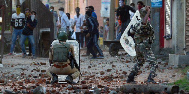 An Indian security offciers throws a stone to Kashmiri protestors during a clash in Batmaloo area of...