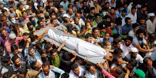 Kashmiri men carry the body of Riyaz Ahmad, a civilian, who according to local media was killed by pellets...