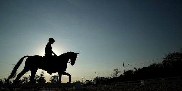 Alex Hua Tian of China works out on his horse at the Olympic Equestrian Center ahead of the 2016 Summer...