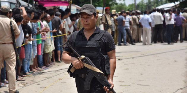 An Indian security personal stands guard near the site of a militant attack on a market at Balajan Tinali...