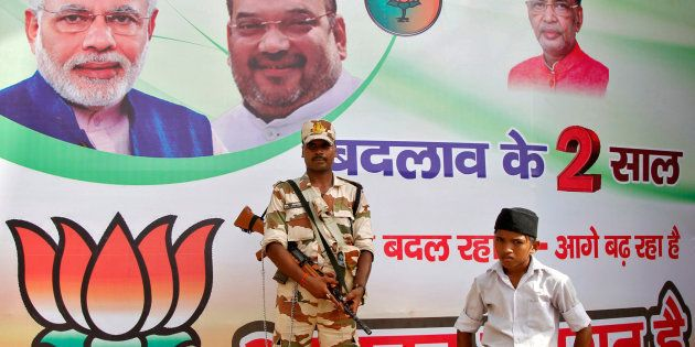A policeman stands guard as a volunteer (bottom R) of the Hindu nationalist organisation Rashtriya Swayamsevak...