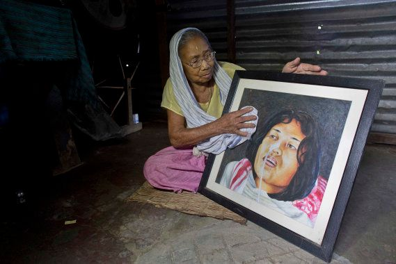 Irom Sakhi Devi, 84, mother of Indian activist Irom Sharmila, holds and cleans a portrait of her daughter...