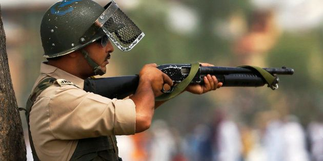 A policeman aim his pellet gun at protesters during a protest in Srinagar, Indian controlled Kashmir,...