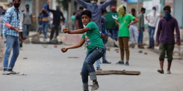 A protester throws stones towards the Indian police during a protest in