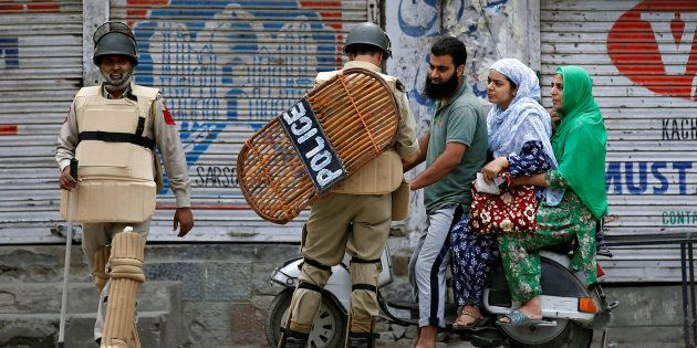 An Indian policeman checks the identification cards of a family during a curfew in Srinagar, August 8,