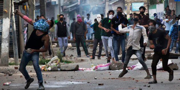 Kashmiri Muslim protesters throw stones at Indian security personnel during a protest in