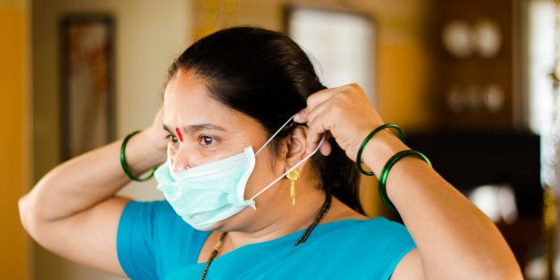 Sneha Avare, a domestic worker at MyDidi, putting on a mask before starting a cleaning