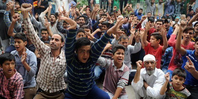 Kashmiri people gesture as they shout anti-Indian and pro-freedom slogans during a