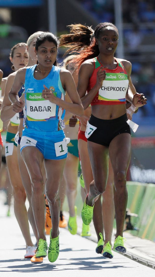 Kenya's Beatrice Chepkoech, right, and India's Lalita Babar, center, competes in a women's 3000-meter