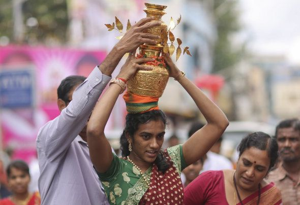 Indian badminton player P V Sindhu carries on her head decorated pots filled with cooked rice as an offering...