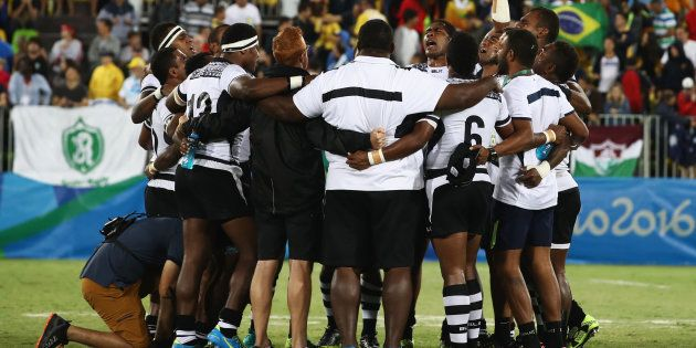 Fiji players and staff huddle as they win gold after the Men's Rugby Sevens Gold medal final match between...