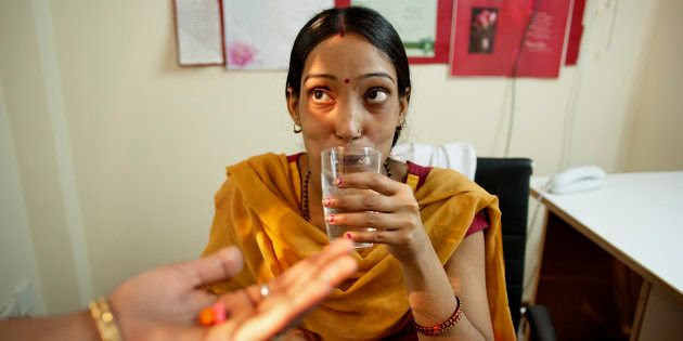 A surrogate mother in New Delhi takes one of her many daily doses of medicine.Eggs from Europeans, semen...