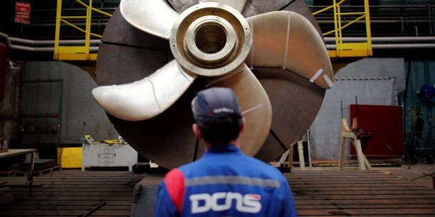 An employee looks at the propeller of a Scorpene submarine at the industrial site of the naval defence...