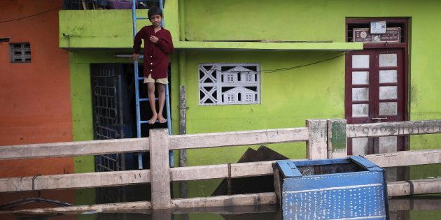A boy stands on a ladder outside his flooded house in Chennai, India, December 5, 2015. REUTERS/Anindito...