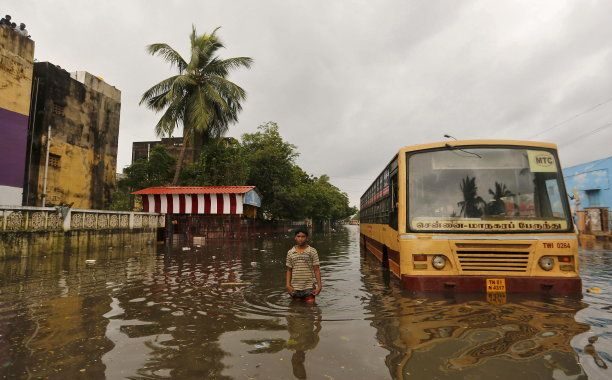 A boy wades next to a partially submerged bus in a flooded locality in Chennai, India, December 5, 2015....
