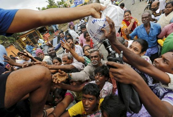 Flood-affected people raise their hands to receive free food being distributed by Indian Navy personnel...