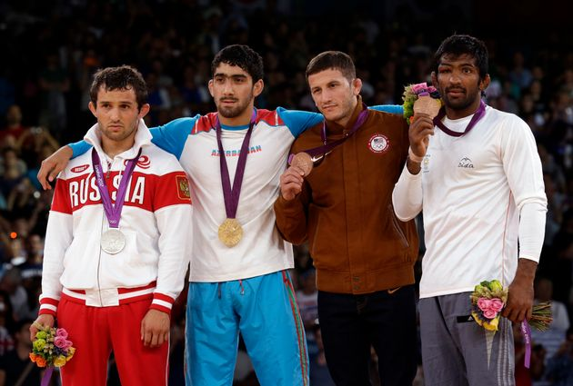 [File Photo] (L-R) Silver medalist Besik Kudukhov of Russia, gold medalist Toghrul Asgarov of Azerbaijan,...